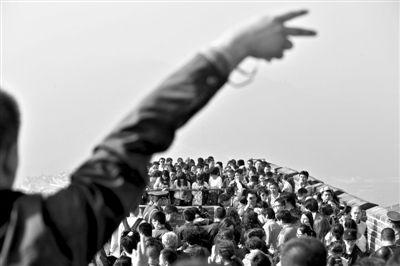 10月4日,游客在好汉坡上摆手势拍照留念,背景是如织的人流。新京报记者 周岗峰 摄