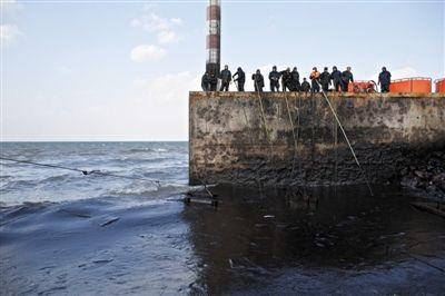 昨日,山东青岛,清污人员正在海边清理油污。