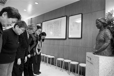 """昨日,北师大女附中的几位""""老三届""""学生给文革中遇难的卞校长雕塑鞠躬默哀。(左二:刘进;左三:宋彬彬) 新京报记者 韩萌 摄"""