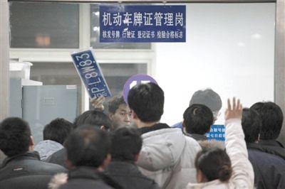2010年12月22日,崔各庄附近检测场办公大厅内,工作人员正在发放车牌。昨日,副市长张延昆表示,北京没有车牌拍卖计划。新京报资料图片/王嘉宁 摄