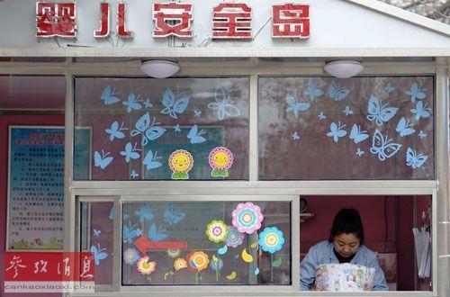 """资料图片:3月3日,西安儿童福利院的工作人员整理放置在""""婴儿安全岛""""内的被褥。新华社记者 李一博 摄"""