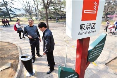 """月1日,北京动物园,两位游客在吸烟区抽烟。""""京版""""控烟条例草案拟规定室内公共场所全面禁烟。新京报记者 薛珺 摄"""