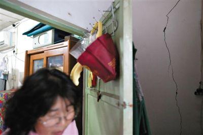 """5月8日,被称为""""白纸坊第一危楼""""的西城区永乐里1号楼,一户居民家中,墙上多条裂缝中的一条,几乎分割了整面墙"""