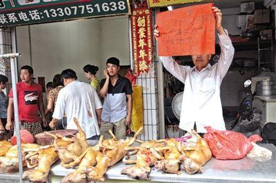 """21日,玉林专门卖狗肉的垌口市场,一位玉林人举起纸牌,称""""吃不吃狗肉各有自由选择的权利""""。"""