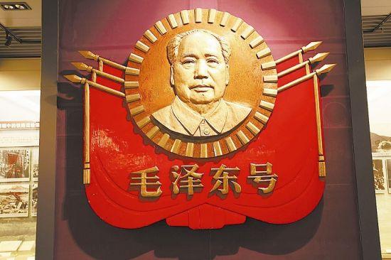 """该车徽为纯铜制造,重370公斤,车徽上有镀金的毛泽东浮雕塑像、六面红旗和""""毛泽东号""""四个字,是悬挂在换型后的东风4型0002号内燃机车上的,被定为国家三级文物。"""