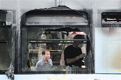 工作人员在发生燃烧后的公交车内查看现场。新华社发