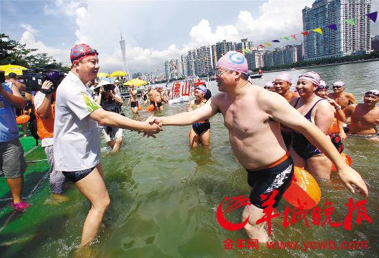 佛山市代市长鲁毅(右)游上了岸,陈建华笑着步入及膝的水,与鲁毅亲切握手 羊城晚报记者 郑迅摄