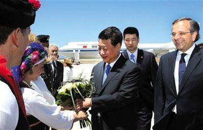13日,习近平抵达罗德岛迪亚哥拉斯机场时,身着当地传统服装的希腊青年前来献花。新华社记者 兰红光 摄