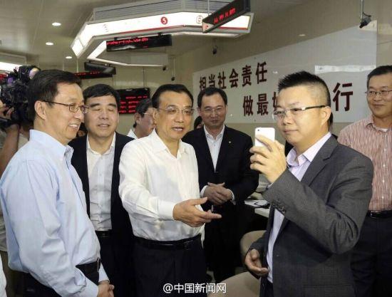 """18日,在中国银行上海自贸区分行办理业务的吴先生通过手机视频,将正在该行考察的李克强总理""""秀""""给香港客户。"""