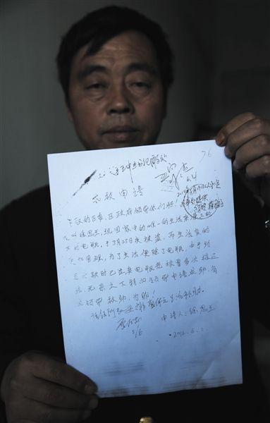 10月15日,北京,安徽宿州人黄新民拿着《求救申请》。申请落款是他爱人徐思兰签的名。 新京报记者 尹亚飞 摄