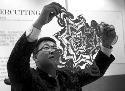 """剪纸艺术家王磊审视自己的作品。昨天,APEC主要会场之一,国家会议中心的装饰布置充满""""京味儿""""。新华社发"""