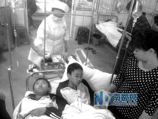 昨日下午,塘厦镇人民医院急诊科,病床不够,塘厦初级中学的初三学生和初一学生挤在一张病床上。南都记者 寇金明 摄