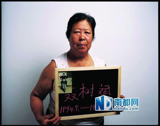 去年9月,河北省高院宣布王书金案与聂树斌案无关后,聂树斌母亲举着儿子的照片表示不服。南都记者 郭现中 摄