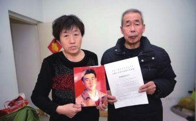 昨天,李三仁、尚爱云拿着儿子呼格吉勒图照片与《国家赔偿决定书》。中新社发