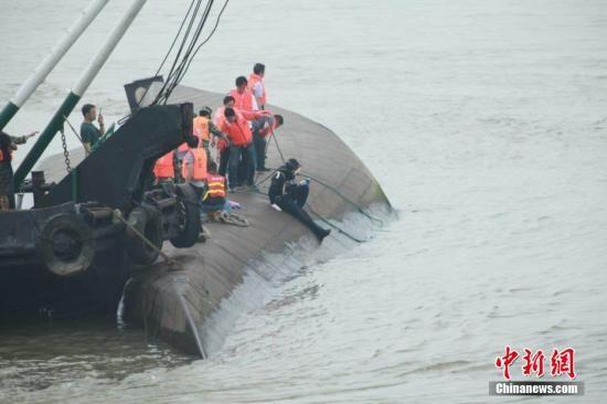 """6月2日下午,湖北监利沉船地点,救援人员在倾覆的客船附近继续进行搜救。6月1日21时30分许,重庆东方轮船公司所属旅游客船""""东方之星""""轮在由南京驶往重庆途中,突遇龙卷风发生翻沉。据初步统计,事发客船共有458人,其中旅客406人。"""