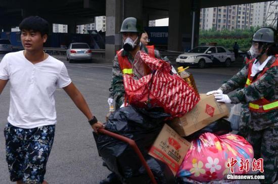 8月18日下午,一队防护人员帮助居民搬运大发5分PK10用品离开。中新社发 贾国荣 摄