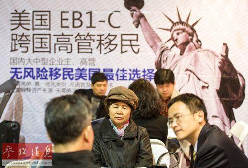资料图片:一家公司工作人员在北京春季房展会向参观者介绍海外投资移民情况。