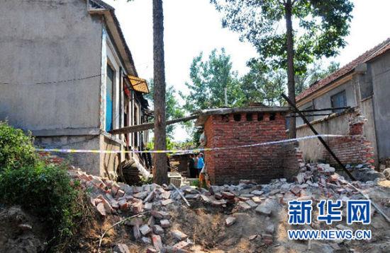 山东平邑县一农民被烧死事件调查死者张纪民家的西侧院墙被推倒,并已拉上了警戒线 新华社记者张志龙摄