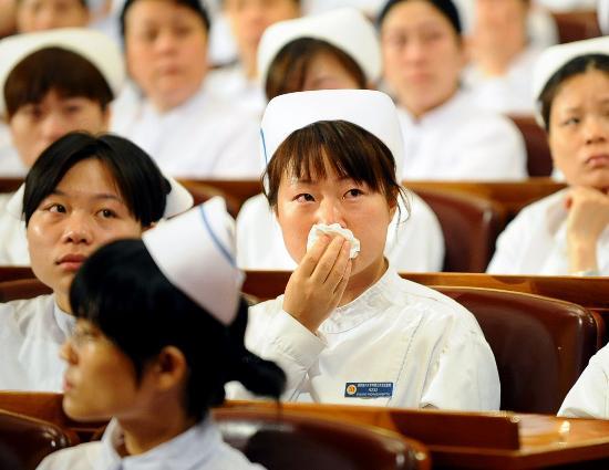 图文:一名医护人员被报告团成员的发言感动