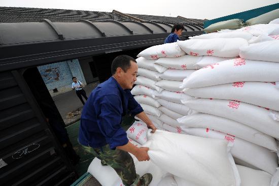 图文:工人在向货运列车上装运救灾大米