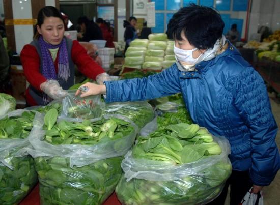 图文:一位市民在一家社区菜市场内选购蔬菜