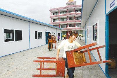 3月20日,盈江县民族小学的部分学生家长正在帮助学校往新搭建的板房