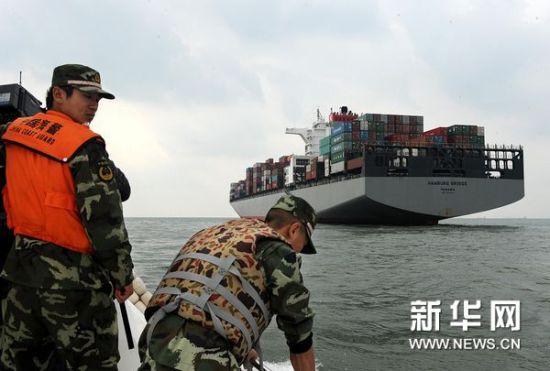 """10月29日,山东海警二支队巡逻艇在外轮相撞事故海域搜寻,远处为发生碰撞的巴拿马籍货轮""""HAMBURG BRIDGE""""轮。"""