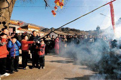 图为2012年1月22日胡锦涛在北京与民众共迎新春和山村孩子放鞭炮