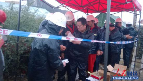 青岛市开发区秦皇岛路,中午12点。图为救援清理现场的后勤人员在发放盒饭。(摄影 彭亮)