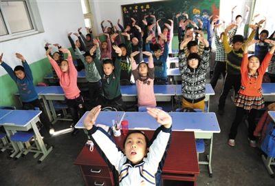 """12月11日,学生在教室内演示""""防霾""""武术健身操。全国各地遭受雾霾笼罩,石家庄光明路小学为此发明了一套""""防霾""""武术健身操。图/CFP"""