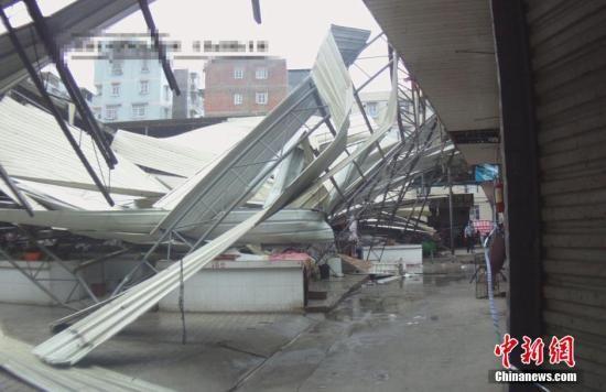 """7月19日上午11点35分,在第9号强台风""""威马逊""""的影响下,广西南宁市五一西路富宁综合农贸市场的大盖棚发生坍塌,所幸南宁巡警疏散及时,事件无人员伤亡。中新社发 劳运荣 摄"""