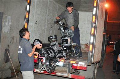 27日晚,搬家公司员工帮助警方清运收缴的赃车。当天,警方在衙门口旧货市场围捕电动车盗销团伙,清缴了至少100多辆涉案电动车。 新京报记者 王嘉宁 摄