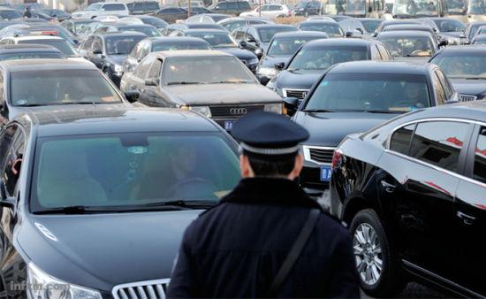 某市政府工作会议后,公务车排队涌出停车场。 (CFP/图)