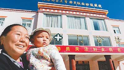 云南香格里拉县的卓玛高兴地参加新型农村合作医疗.
