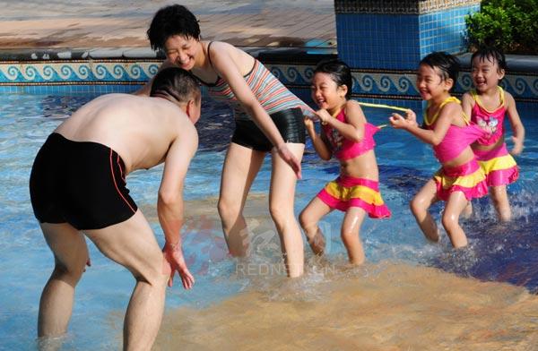 三胞胎女孩和父母在游泳池戏水图