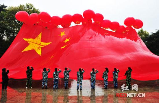 18只红色气球牵引着一面18米长的五星红旗高高升起图片