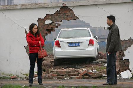 am6219的小轿车,突然冲向人行道,撞垮一小区围墙后停下,幸无人员伤亡.