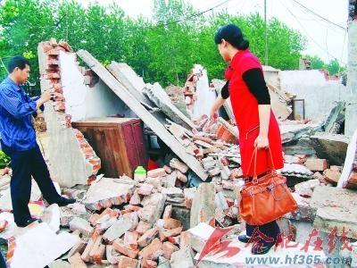 陈俊胜夫妇站在遭毁的屋前欲哭无泪