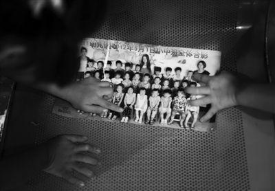 昨晚10时许,北京儿童医院,两名女童正在班级合影照片上指认其他受害者。廊坊一家幼儿园的管理人涉嫌猥亵园内多名女童。昨晚,三名女童及家长在志愿者的帮助下进京检查。新京报记者 尹亚飞 摄