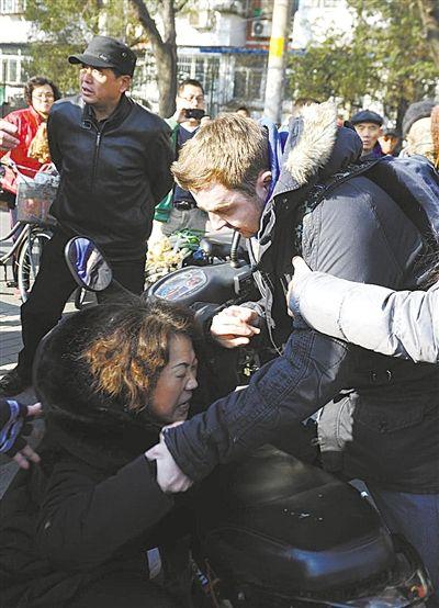 被撞中年妇女抱住撞人后爆粗口的外籍男子。