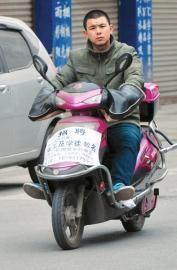 一名小伙骑着贴有招聘单的电瓶车走街串巷招人。