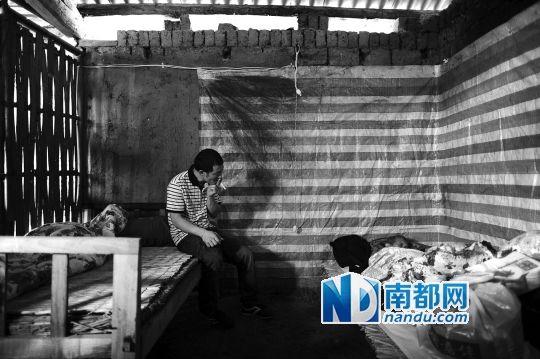 4月17日杨九将母亲安顿好后坐在床沿吸着烟,如今母亲过世,自己被确诊患精神分裂症。 南都记者 梁清 摄