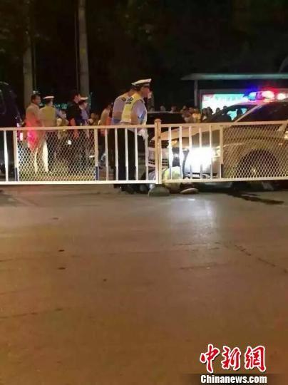 图为辅警在执行酒后驾驶专项治理中被一无牌奥迪轿车顶在前盖上狂奔1000米被逼停后,掉落车前。