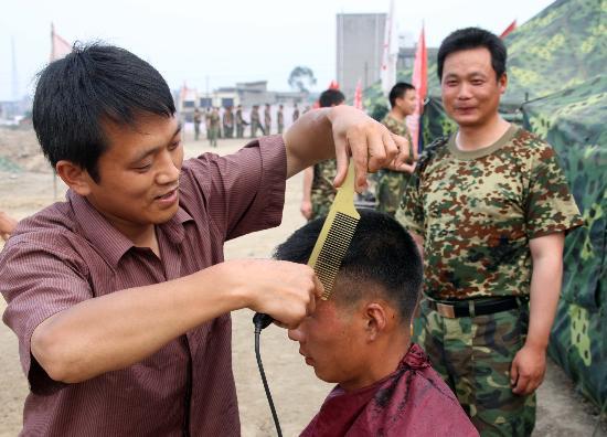 图文:志愿者在为部队官兵理发
