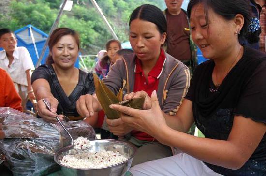 图文:汶川双河村村民在救灾帐篷前包粽子