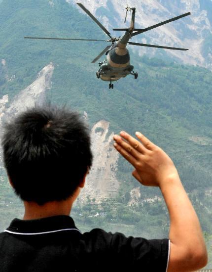 图文:一名少年向一架参加救灾的直升机敬礼