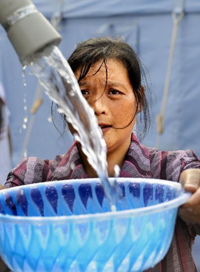 图文:妇女在汶川映秀镇居民临时安置点取水