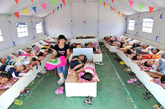帐篷幼儿园的幸福时光 朱红老师在看护午休的幼儿园小朋友(6月12日摄)。 汶川大地震发生后,成都军区驻滇某部捐款捐物,在四川省北川县擂鼓镇建起一所帐篷幼儿园,13名志愿者姑娘成为园里200个孩子的临时老师。孩子们在这里安心生活、学习,度过一段难忘的幸福时光。 新华社记者 何俊昌 摄