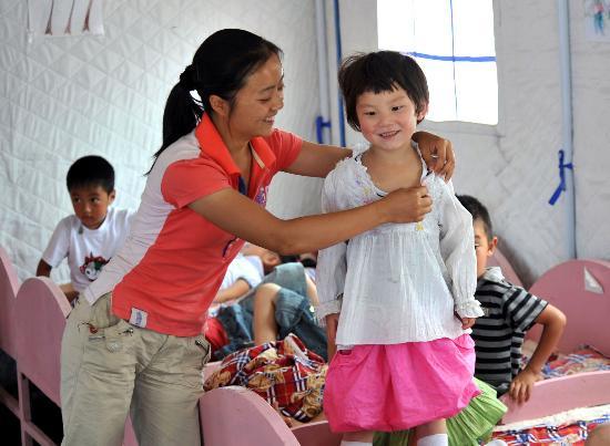 图文:夏艳老师帮午休后的幼儿园小朋友穿衣服