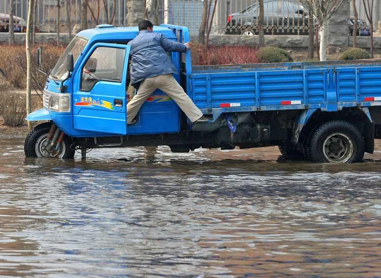图文:男子从农用三轮车爬出拽车